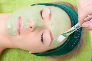 Beauty treatment concept. Woman relaxing in spa salon. Cosmetician applying clay facial mask at female face. Body care healthy lifestyle.
